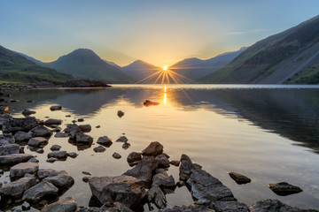 Peaceful view of Wastwater in the Lake District as the sun rises through mountains. Wall mural