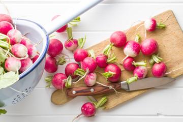 Fresh radishes on old cutting board.