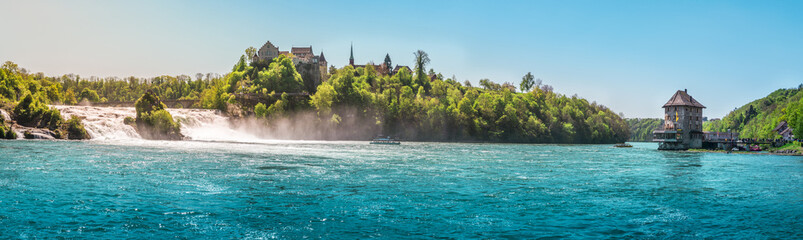 The Rhine Fall on a sunny day - Panorama with the Rhienfall, the Laufen castle and Worth Castle, while boats navigate the blue waters of the river, in Switzerland.