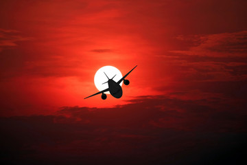 Closeup of the airplane silhouette on the beautiful sun and red sky.