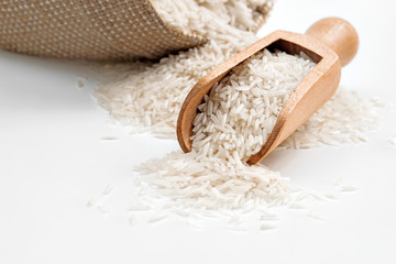 Raw long rice in wooden spoon and sack on white background. Close up, high resolution product.