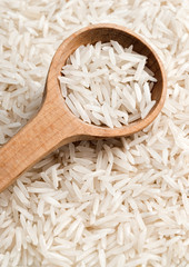 Raw rice in wooden spoon.  Close up, high resolution product.