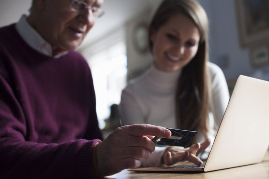 Granddaughter Helping Grandfather To Make On Line Purchase