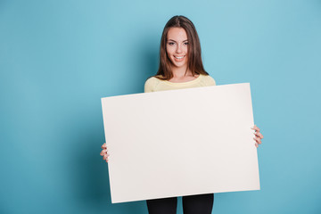 Pretty young woman holding empty blank board over blue background