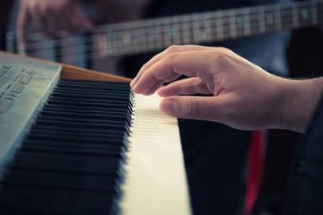 Hand playing music keyboard and bass guitar player in the background. Detail form a concert.