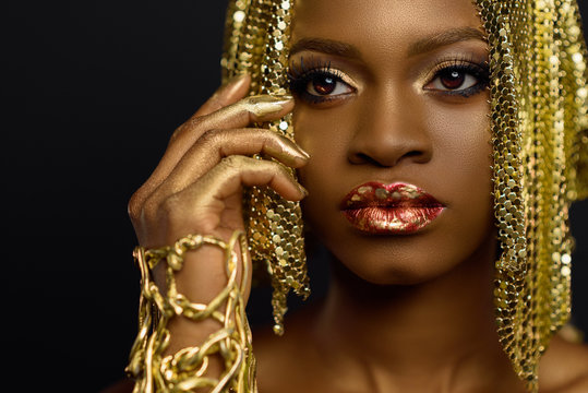 Sexy african american female model with glossy makeup and golden wig. Face art.
