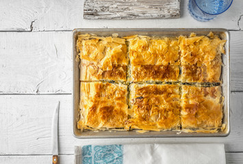 Greek pie spanakopita in the metal pan  with table ware top view