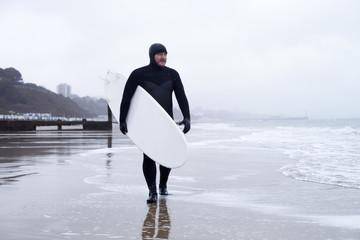 Surfer Wearing Wetsuit Carrying Board Along Beach