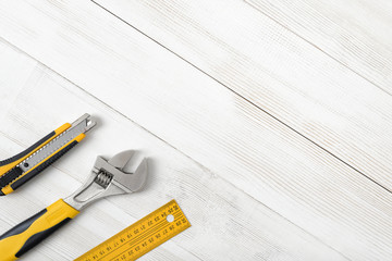Construction tools including centimeter ruler, wrench and cutter placed in the right down corner on wooden surface with open space.