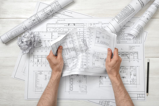 Close-up hands of architect tearing a bad drawing