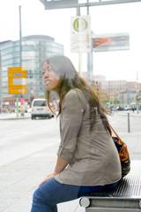 Deutschland, Berlin, junge Frau wartet an der Bushaltestelle, To