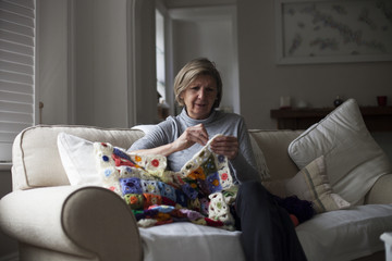 Close Up Of Woman Sitting On Sofa Making Crochet Blanket