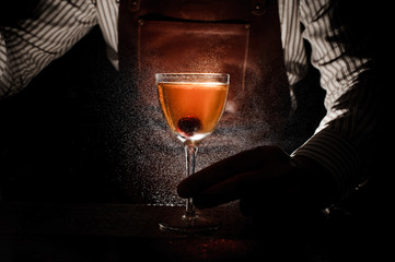Expert barman is spraying on cocktail close up
