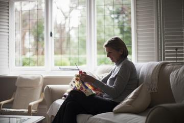 Woman sitting on sofa and knitting