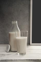 Milchflasche und gefülltes Glas mit Milch auf der Fensterbank