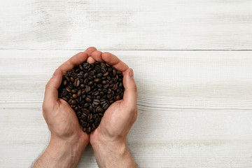 Close-up hands of man holding a handful coffee beans with copy space