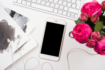 smartphone, computer keyboard and fesh pink flowers on white tab