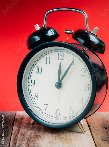 retro alarm clock with 12 oclock and five minute on white background retro
