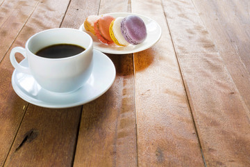 Black coffee in white cup with macaroon on old wood table.