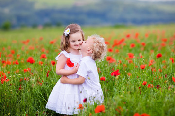 Kids playing in red poppy flower field
