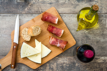 Spanish serrano ham, cheese and sausage on a rustic wooden background