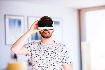 Man wearing virtual reality goggles, standing in living room