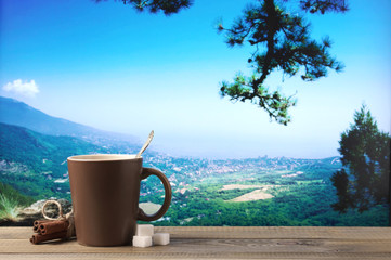 Coffee cup against mountain landscape