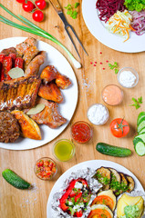 High Angle View of Grilled Meal of Steak, Chicken and Vegetables Spread Out on Rustic Wooden Table