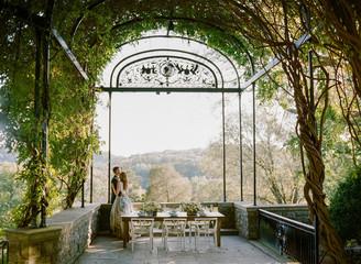 Bride and groom on patio underneath arch