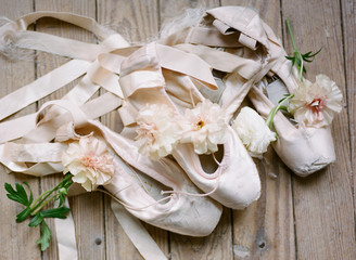 Ballet shoes on wooden floor with fresh flowers