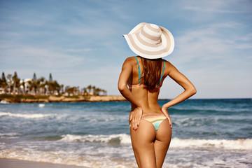 Sexy back of a elegant tanned woman relaxing in bikini on sea background. Sexy buttocks. Ayia Napa, Cyprus island, Mediterranean Sea. Retro vintage toned image, film simulation.