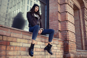 Outdoor lifestyle portrait of pretty young girl, wearing hipster swag grunge style on urban background. Wearing hat and jeans denim. Spring fashion woman. Toned style instagram filters.
