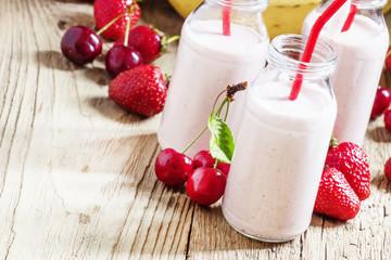 Strawberry-cherry milkshake with banana, wood background, select