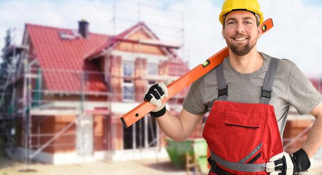 Handwerker/ Bauarbeiter vor einem Neubau Einfamilienhaus