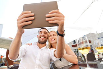 happy couple taking selfie with tablet pc at cafe