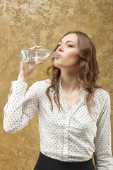 attractive girl drinking and slopping out water on her blouse