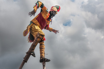 Man in jester costume balancing on stilts