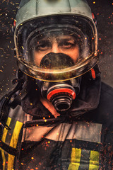 Portrait of firefighter in oxygen mask in a sparks.