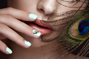 Beautiful girl with manicure design and peacock feather on her face. Art nails.