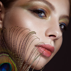 Beautiful girl with bright colored makeup and peacock feather on her face. Beauty. Close-up