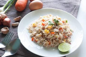 A dish of fried rice, carrot and egg on brown fabric, spoon, fol