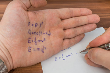 Student is cheating during exam with cheat sheet with formula written on hand.
