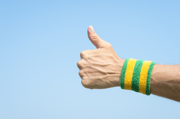 Brazilian athlete wearing Brazil colors green and yellow wristband holding thumbs up against blue sky