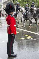 Guard stands at attention as a horse-drawn procession carrying Queen Elizabeth II toward Buckingham Palace passes along a rainy street in London, UK
