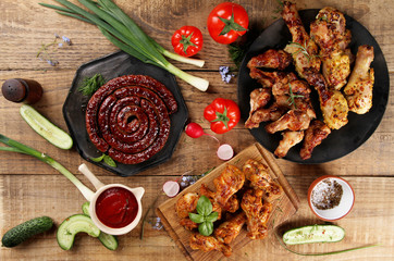 Grilled sausage, chicken leg and wings with vegetables