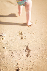 Baby's footprints in the sand, with focus on the footprints