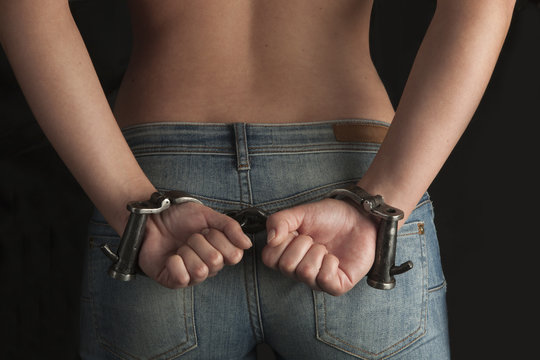 naked woman in handcuffs on black background