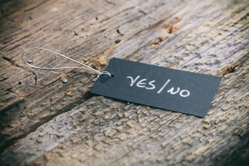 "Closeup of pricing tag with twine and ""Yes/No"" text on wooden background"