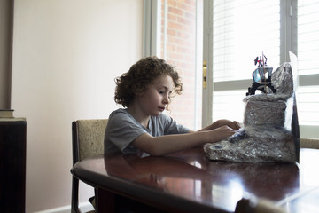 Boy Builds Model Lunar Landscape For School Project At Home