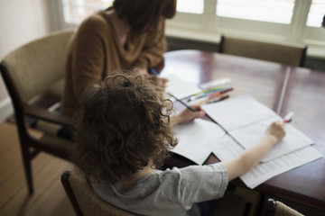 Mother And Son At Home Sitting At Table And Doing Homework